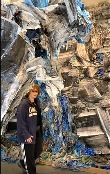 Yaniv stands under a mixed-media installation
