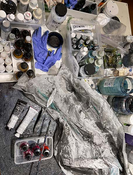 Yaniv's studio table holds paints, material, and other necessary tools.